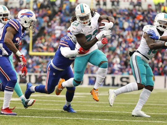 Miami Dolphins running back Jay Ajayi (23) runs inside the five to set up a first quarter touchdown as the Buffalo Bills host the Miami Dolphins at New Era Field in Orchard Park, N.Y. on Saturday, Dec. 24, 2016. (Al Diaz/Miami Herald via AP)