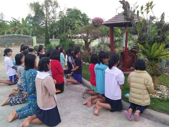 Students and others at a school in northern Thailand gather for an outdoor Catholic prayer service. Springfield-based Thailand Little Ones is raising money to build a chapel at this school.