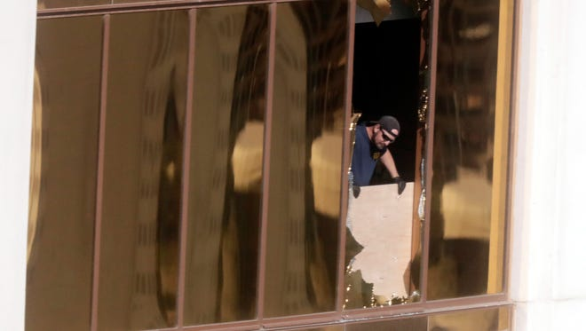 Agents from the FBI use binoculars from the broken window where a gunman opened fire at the Mandalay Bay hotel, Wednesday, Oct. 4, 2017, in Las Vegas.
