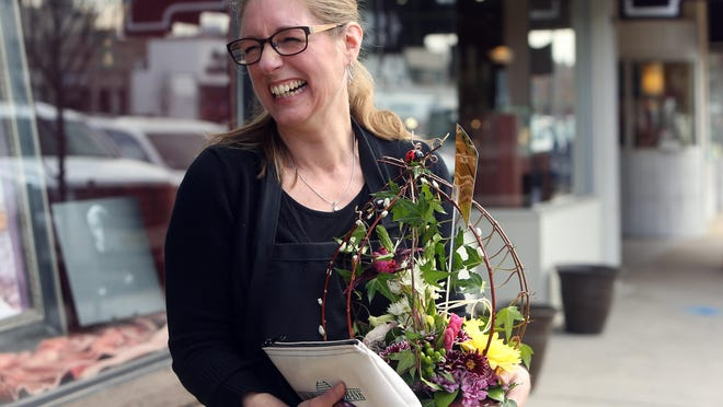 Local store owner Stephanie Meehan of Smartworld Coffee reacts to getting 'Flower-bombed.'