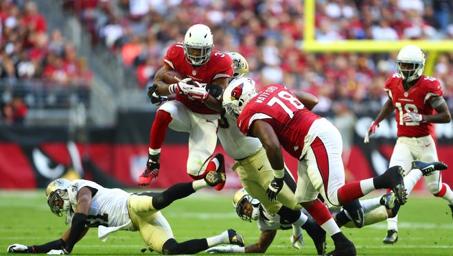 Arizona Cardinals running back David Johnson (31) leaps a defender as he runs the ball against the New Orleans Saints in the first half at University of Phoenix Stadium. The Saints defeated the Cardinals 48-41.