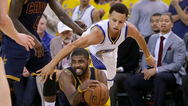 Cleveland Cavaliers guard Kyrie Irving, bottom, is guarded by Golden State Warriors guard Stephen Curry during the second half of Game 1 of basketball's NBA Finals in Oakland, Calif., Thursday, June 4, 2015. (AP Photo/Ben Margot)