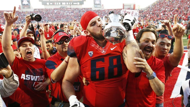 Arizona's Mickey Baucus kisses the Territorial Cup after defeating Arizona State 42-35 on Friday, Nov. 28, 2014 in Tucson, AZ.