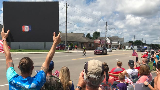 More than 50 of Joe Lawhorn's extended family and friends cheer the rider as he nears the East Main Street timing station in the Race Across America.