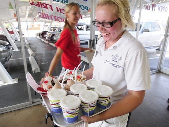 Car hop Becky Ruppel takes an order to a customer at