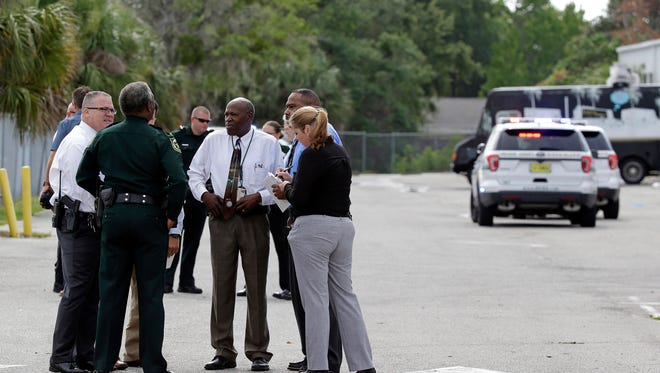Authorities confer near the scene of a shooting where they said there were multiple fatalities in an industrial area near Orlando, Fla., Monday, June 5, 2017. The Orange County Sheriff's Office said on its official Twitter account that the situation has been contained.