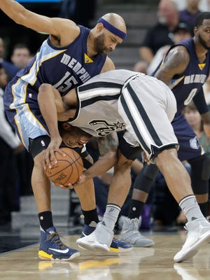 San Antonio Spurs forward Kawhi Leonard (2) crashed into Memphis Grizzlies guard Vince Carter (15) as he tries to drives to the basket during the first half of Game 1 of a first-round NBA basketball playoff series, Saturday, April 15, 2017, in San Antonio.
