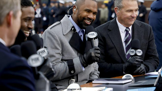 """Analyst Charles Woodson, left, and former Ohio State coach Urban Meyer chat during a broadcast of Fox Sports' """"Big Noon Kickoff"""" before the Ohio State-Michigan game in 2019. The loss of the 2020 season will cost Ohio State tens of millions in TV revenue."""