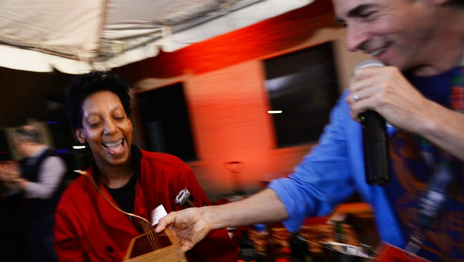 Gregory Kallenberg hands Tootie Morrison the golden fork trophy when she won the Food Prize Saturday evening.