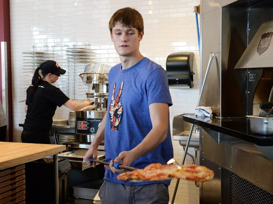 Timothy Landau pulls a hot pizza from the oven at Mod Pizza on Monday, October 24, 2016.