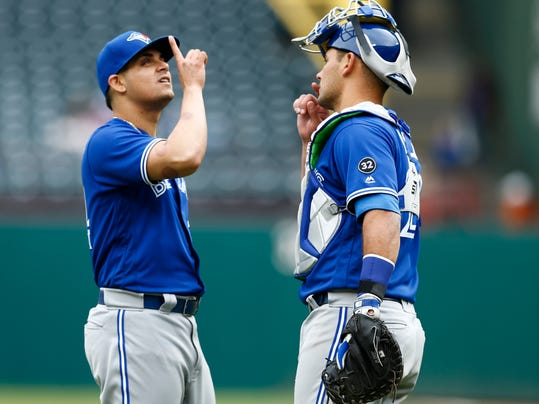 Toronto Blue Jays relief pitcher Roberto Osuna, left, and catcher Luke Maile celebrate their win over the Texas Rangers following a baseball game, Sunday, April 8, 2018, in Arlington, Texas. (AP Photo/Jim Cowsert)