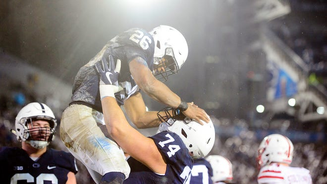 Penn State's Saquon Barkley gets a lift from Steve Gonzalez after scoring a touchdown against Nebraska in the first half of an NCAA Division I football game Saturday, Nov. 18, 2017, at Beaver Stadium. Penn State leads Nebraska 42-10 at halftime.