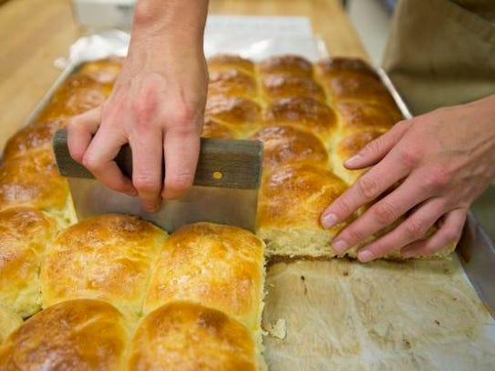 Rolls of brioche are cut at Ingrained Bakery in Wellington