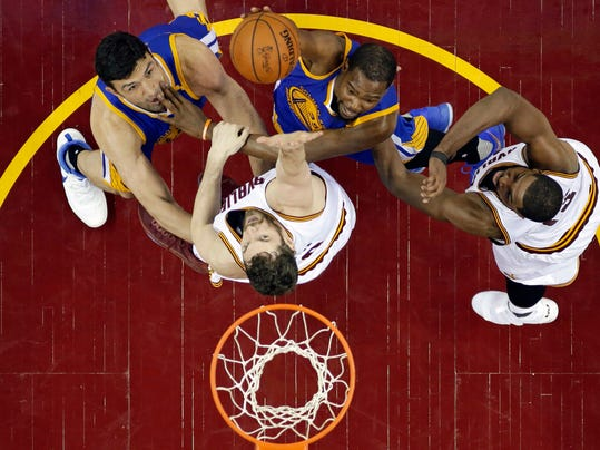 Golden State Warriors' Kevin Durant, second from left on top, drives to the basket against Cleveland Cavaliers' Kevin Love and Tristan Thompson, right, during the second half of Game 4 of basketball's NBA Finals, Friday, June 9, 2017, in Cleveland. Warriors' Zaza Pachulia is at left. The Cavaliers won 137-116. (AP Photo/Ron Schwane, Pool)