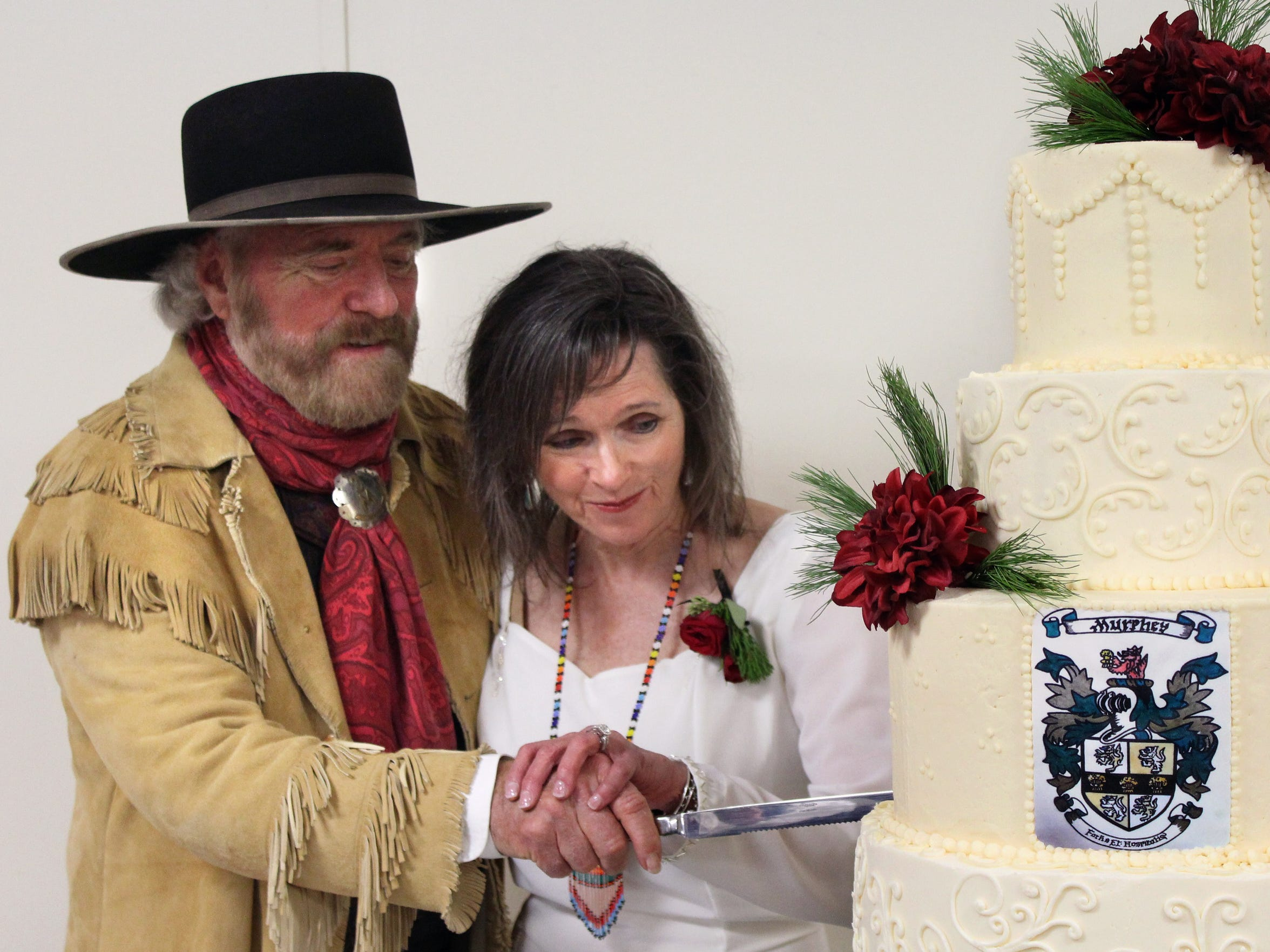 Mr. and Mrs. Michael Martin Murphey spared no tradition at their wedding Dec 16 in Anson, cutting a cake adorned with the Murphey crest.