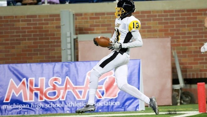 Detroit Martin Luther King Ambry Thomas walks in for a touchdown after cathcing the ball against Lowell, during the second half of the Michigan High School Athletic Association football finals at Ford Field in Detroit on Friday, Nov. 27, 2015.