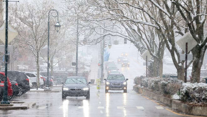 Cars travel north on Erie Avenue through Hyde Park Square, Saturday, March 24, 2018.  A winter weather warning remains in effect until 2 a.m. Sunday for portions of Southeast Indiana, Northeast and Northern Kentucky and Southwest Ohio, including Hamilton County. Butler, Clermont, Brown, and Adams counties are under a winter storm advisory until 2 a.m. Sunday.
