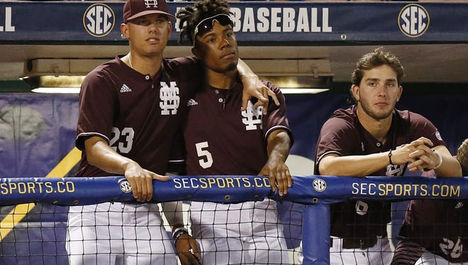 Mississippi State's Austin Sexton, left, and Mike Smith, right, hug in the dugout during the third inning of a Southeastern Conference NCAA college baseball tournament game at the Hoover Met, Thursday, May 26, 2016, in Hoover, Ala. LSU won 6-2. (AP Photo/Brynn Anderson)