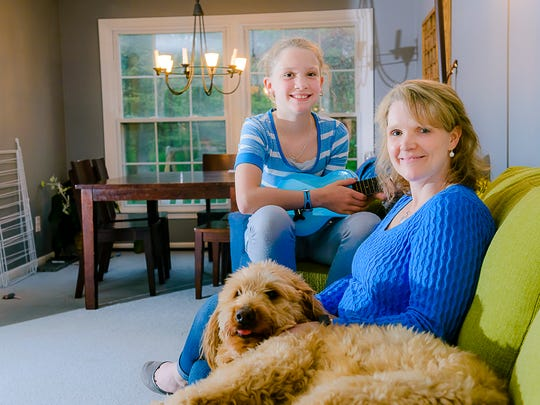 Sara Gooley, right, sits on the couch with her dog Scout while her daughter Madeline plays the ukulele at their home Wednesday in Grand Ledge.  Madeline took lessons with her father Jason before his death.