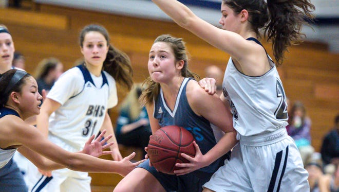 South Burlington's Grace Hoehl, center, drives to the basket against Burlington's Lily Mitchell in Burlington on Tuesday, February 20, 2018.