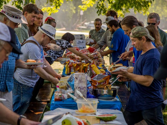 Attendees dig in at the 33rd annual Labor Day Picnic, hosted by the Tompkins County Worker's Center.