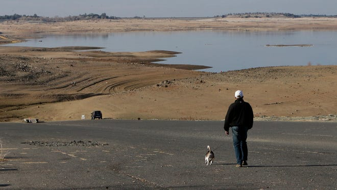 A visitor to Folsom Lake, Calif., walks his dog down a boat ramp that is now several hundred yards away from the water's edge on Jan. 9, 2014.