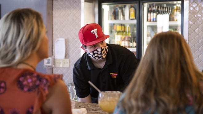 Jared Pendergrass takes a to-go order behind the bar at Albarran's Mexican Bar & Grill in Lubbock on May 1, the first day restaurants were allowed to reopen at reduced capacity in Texas after being shut due to the coronavirus pandemic. Lubbock officials haven't imposed penalties for failing to comply with Gov. Greg Abbott's mask mandate.