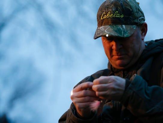 Joe Brooks ties a fly onto his fishing line during