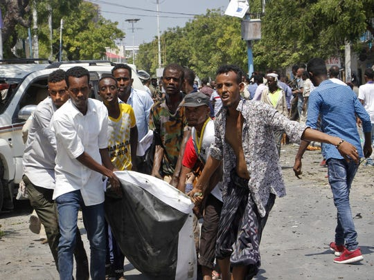 Somalis carry a man who was wounded after a blast outside
