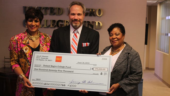 The United Negro College Fund's Justine Boyd, left, and Rosalind D. McGinnis, right, accept a donation from Jim Sherman on behalf of his late uncle, Jerry B. Sherman.
