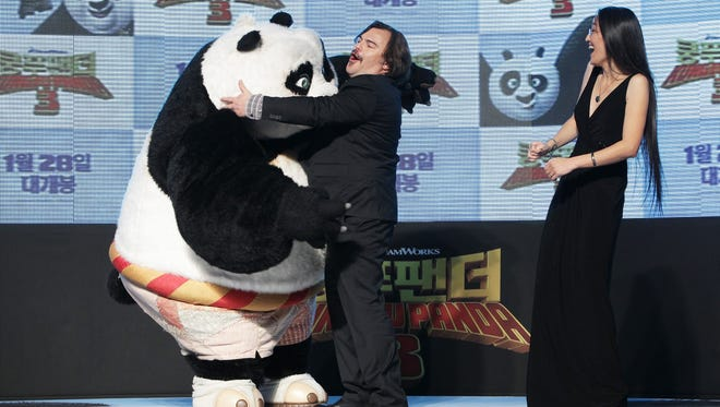 """Jack Black, left, and director Jennifer Yuh, right, attend the premiere for """"Kung Fu Panda 3"""" Wednesday, in Seoul. Comcast reached a deal to acquire Dreamworks Animation, creator of the film, the latest in a series of deals that reflect appetite by cable operators for content."""