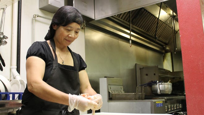 Readers picked Mai's Deli as a favorite small eatery. Here, owner Mai Vang stuffs wings. Her tiny downtown Appleton business sells 100 to 150 wings a day.