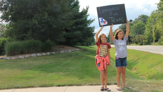 """Oak Creek's Julia Erdmann (left) and Meredith Hacker hold up a """"Lemonade for Texas"""" sign to attract visitors to their lemonade stand. Recently, Rep. Joel Kleefisch proposed a bill to legalize lemonade stands. The bill passed in the Wisconsin Assembly."""