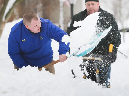 James Farley of Hockessin digs snow from his sidewalk and driveway with the help from his dad, Brandt.