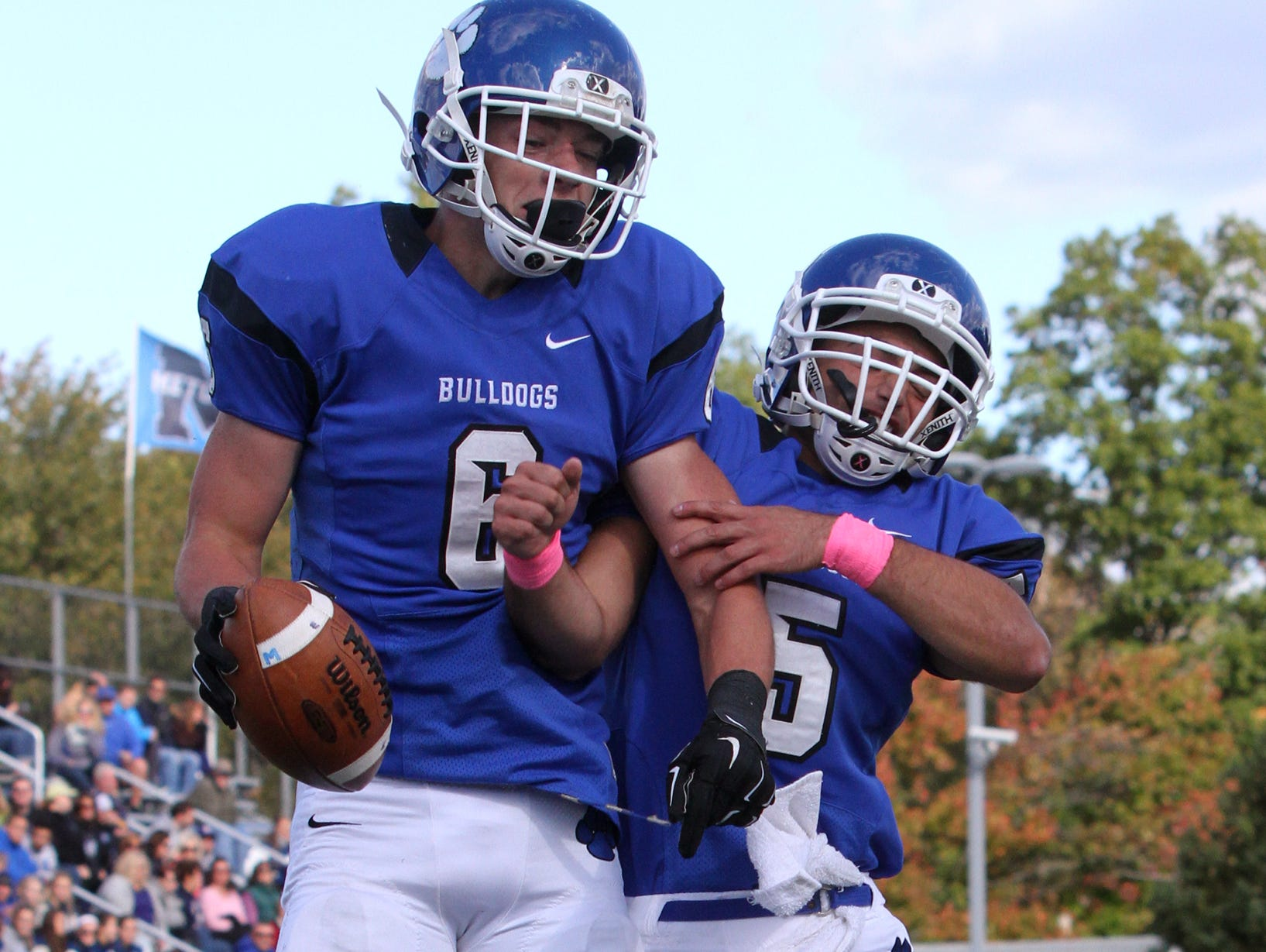 The Blue Jays of Middlesex High School take on the Bulldogs of Metuchen High School in a varsity football game on Saturday October 17,2015. Metuchen's # 6 (left)- Trevor Firgau celebrates his first half touchdown with team mate # 4 (right)- Jake Lebovits.