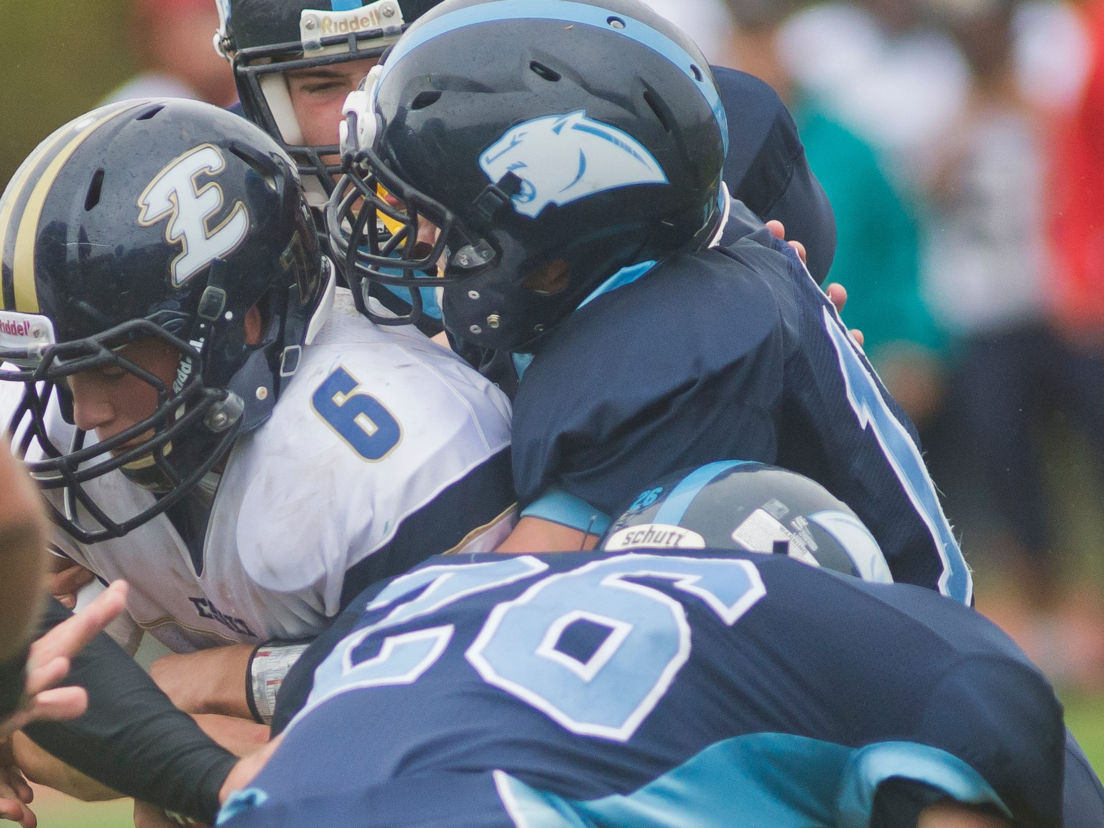 Essex High School's #6 Cody Greene, despite finding holes in MMU's defense for much of first half, gets caught up by the Cougars' #26 Johnny Benvenuto and others during Saturday's game in Jericho.
