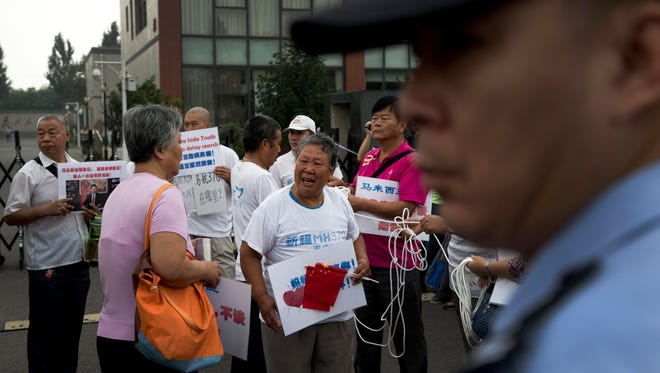A policeman stands watch as relatives of the passengers aboard Malaysia Airlines Flight 370 that went missing on March 8, 2014, protest ahead of a briefing given by the airlines outside a help center in Beijing Friday, Aug. 7, 2015. Families aching for closure after their relatives disappeared aboard the flight vented deep frustration Thursday at differing statements from Malaysia and France over whether the finding of a plane part had been confirmed.