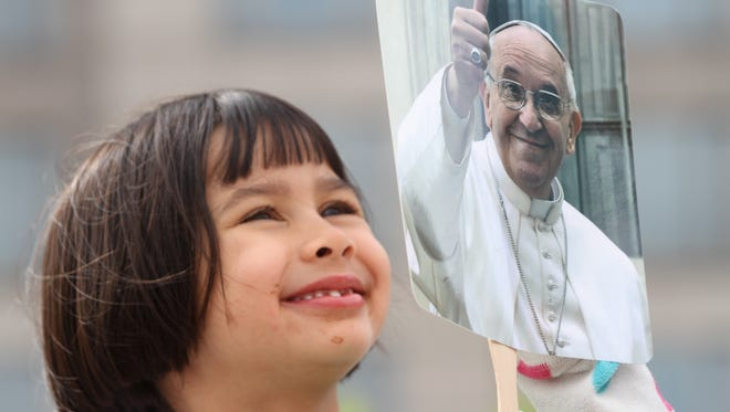 Sabina Samson, age 5, of Delaware, holds a photo of Pope Francis in Philadephia, Sunday, September 27, 2015, prior to a celebration of mass by the Pope Francis at the World Meeting of Families 2015.