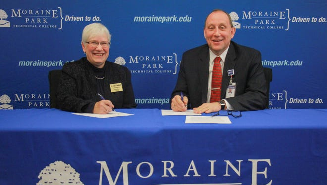 Joyce Caldwell, associate university provost and dean of instruction at Ottawa University, and James Eden, vice president of academic affairs at Moraine Park Technical College, sign a transfer agreement   for their respective colleges.