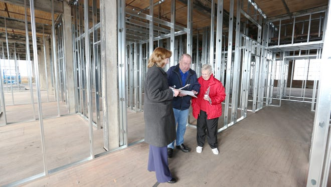 Beth Kohlman, left, Donald and Caroline Glaeser, of Brillion but originally from Manitowoc, take a tour with floor plans at the second floor of the future Artist Lofts on Dec. 17. The Glaesers are thinking about to move back to Manitowoc and the Artist Lofts is a possible option for them.