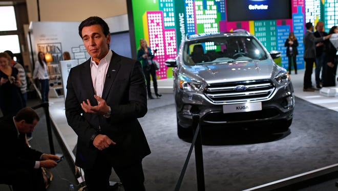 Ford CEO Mark Fields talks during an interview next to the new Kuga SUV car, which features its latest connectivity and driver-assisted technology.