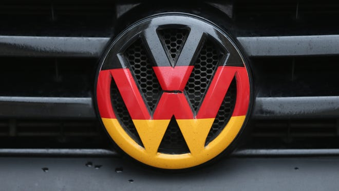 A Volkswagen logo and hood ornament in the colors of the German flag is visible on the front grille of a car on December 17, 2015 in Berlin, Germany.