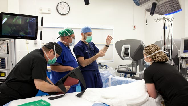 Dr. Richard Farnam describes the sequence of events to his team prior to the surgery that was about to be broadcast live. The team, which included Lorenzo Del Olmo, Mike Thomas and Valeria Torres, gathered around the state-of-the-art surgical bed as they prepared.