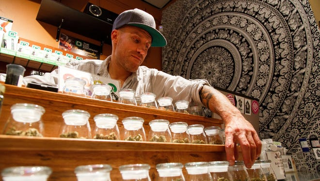 Shane Cavanaugh, owner of Amazon Organics, a pot dispensary in Eugene, Ore., arranges the cannabis display in his store.