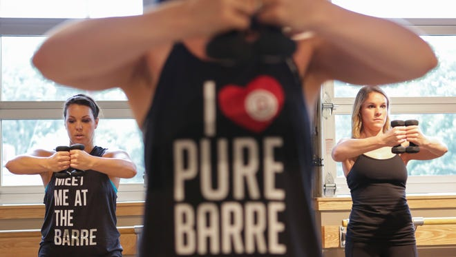 Participants do shoulder toning exercises at the new Pure Barre location near Cherokee Park on Lexington Road.