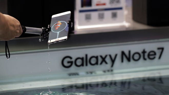 A man tries out the Samsung's latest smartphone Galaxy Note 7 at a roadshow booth outside a shopping mall in Beijing, Thursday, Sept. 1, 2016. Samsung has delayed shipments of Galaxy Note 7 smartphones in South Korea for quality control testing after reports that batteries in some of the jumbo smartphones exploded while they were being charged. (AP Photo/Andy Wong) ORG XMIT: XAW103