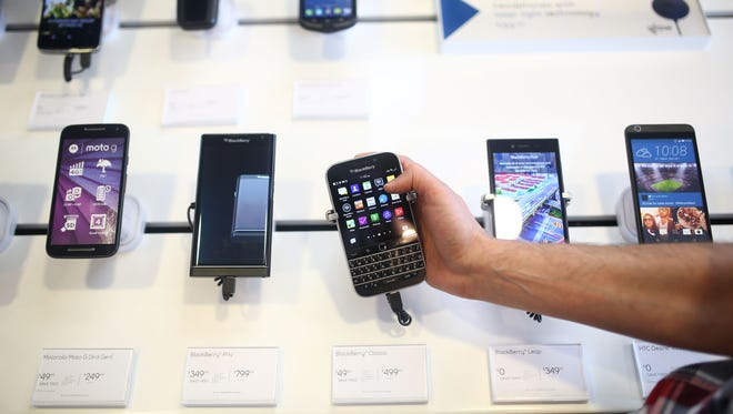 """An employee holds a BlackBerry Classic smartphone at a store in Waterloo, Ontario, Canada, on July 6 BlackBerry, the Canadian company that invented the smartphone and addicted legions of road warriors to the """"crackberry,"""" has stopped making its iconic handsets."""