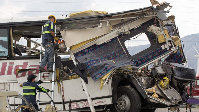 A worker uses a chain saw to cut the wreckage after a bus crash that killed 13 people on Interstate 10 near Palm Springs.