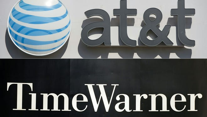 "Tile combination of pictures created on October 21, 2016 shows an AT&T cellphone store in Springfield, Va., and the Time Warner logo on the front of the company's headquarters building in New York.  AT&T's $85.4 billion bid for Time Warner now faces ""uncertain"" timing, an AT&T executive said Wednesday"