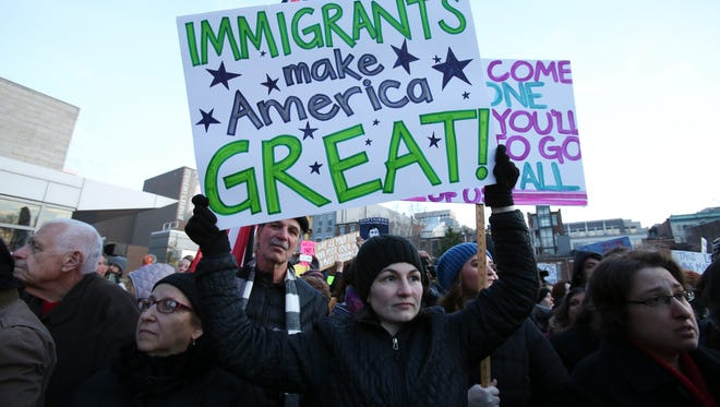 Melissa King held up a sign during the Rally for American Values on the plaza of the Muhammad Ali Center to protest President Donald Trump's recent immigration executive order.Jan. 30, 2017